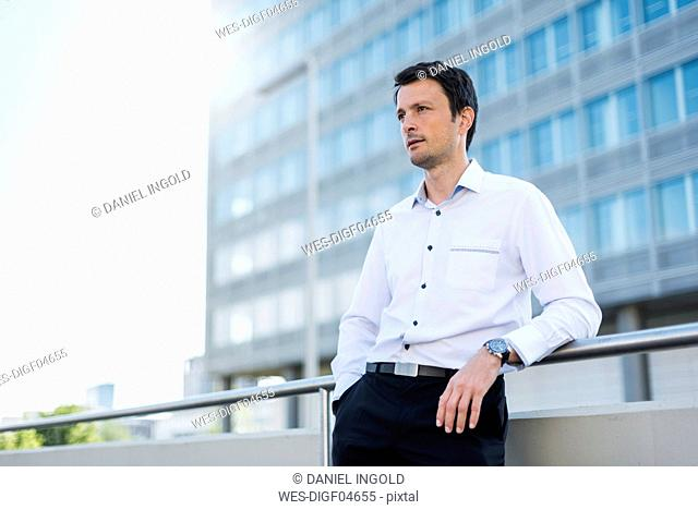 Businessman leaning on railing in the city