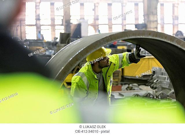 Steel worker examining pipe in factory