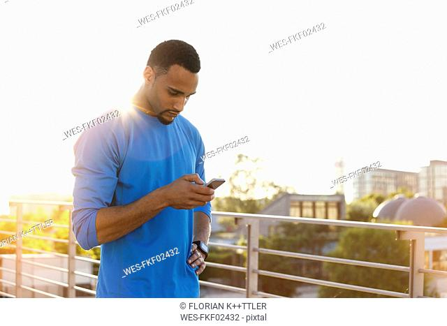 Athlete on bridge in the city checking his cell phone