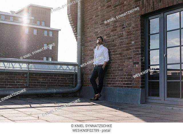 Businessman standing on rooftop terrace, with hands in pockets