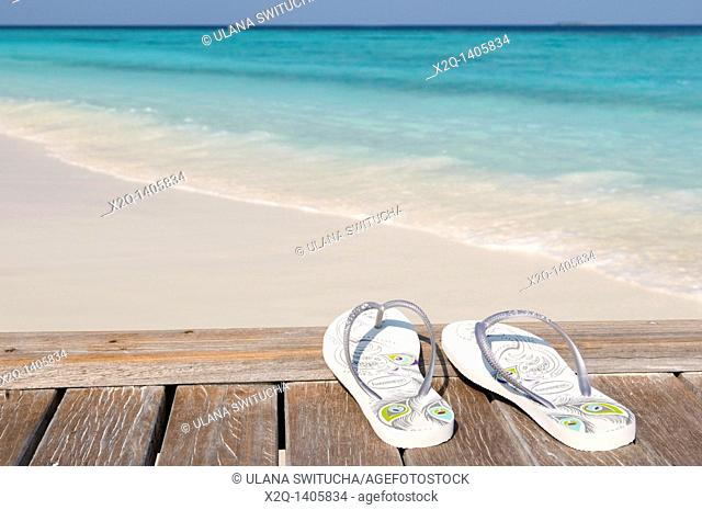 Flip flops on a jetty next to a white sand beach Maldives