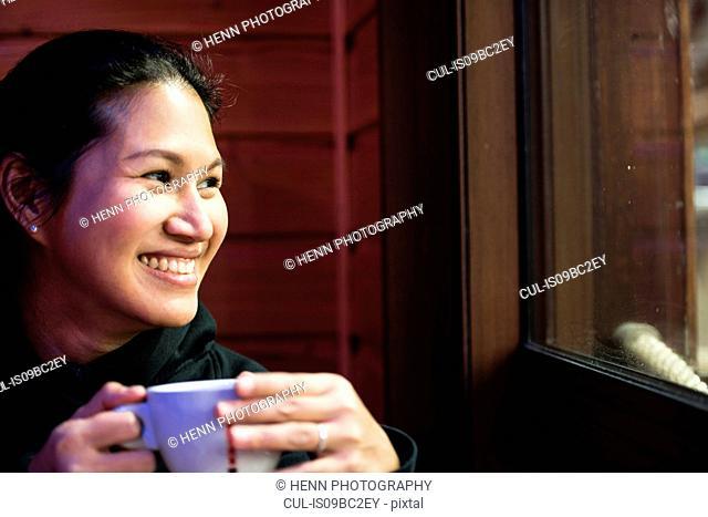 Portrait of woman having a coffee, looking through window