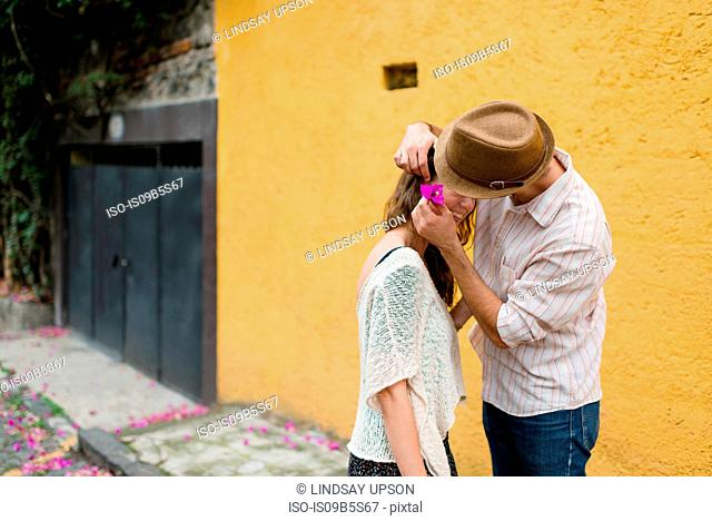 Man putting flower in woman's hair, Mexico City, Mexico