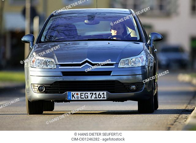 Car, Citroen C4 1.6 16V, model year 2004-, silver/anthracite, Lower middle-sized class, Limousine, driving, diagonal from the front, frontal view, City