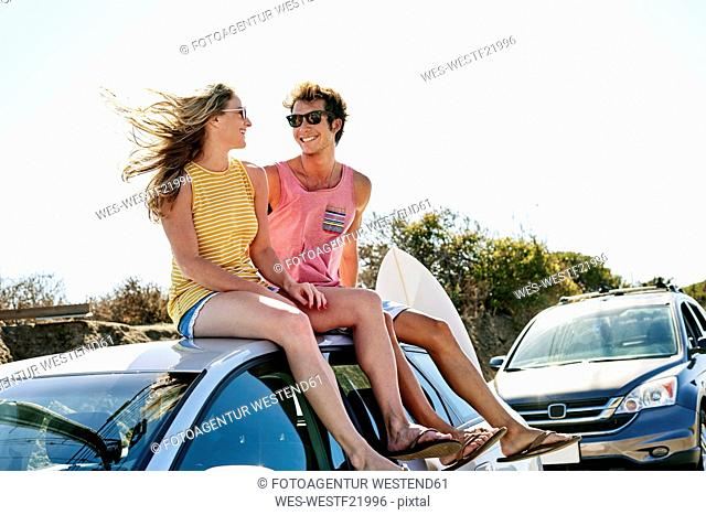 Smiling young couple sitting on car roof