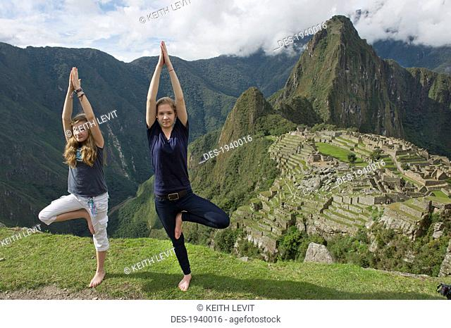 two girls doing a pirouette on a cliff overlooking machu picchu, peru