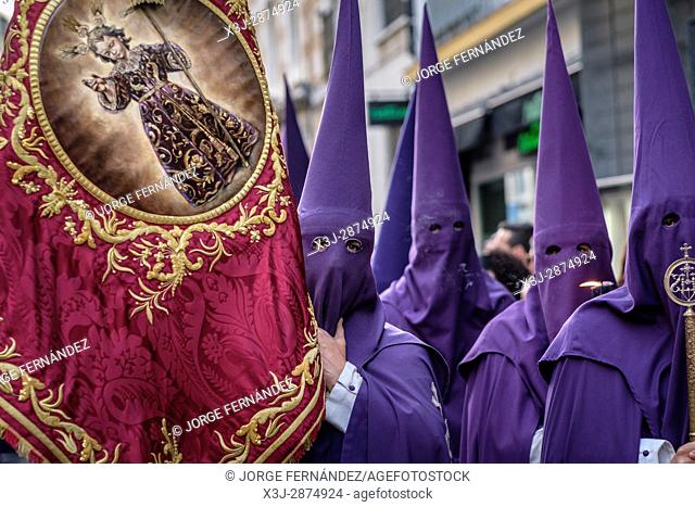 Nazarenos participating in a religious procession, with the traditional robes and hoods and carrying a banner for their brotherhood during Semana Santa (Easter)...