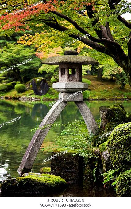 One of the most beautiful gardens in Japan, Kenrokuen, located in Kanazawa, Ishikawa, Japan leg is in the water and the other on land
