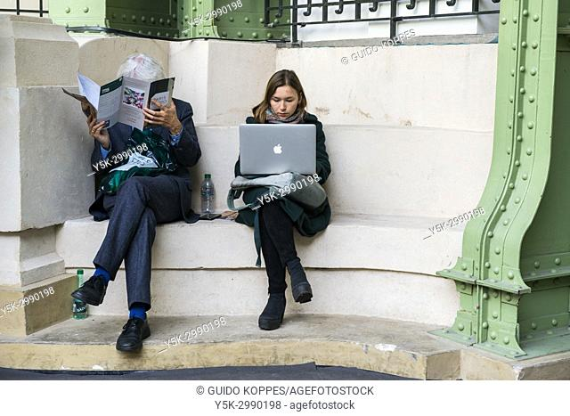 Paris, France. Young adult female working on her notebook computer while sitting inside a niche during Paris Photo Festival accompanied bij a mature adult male...