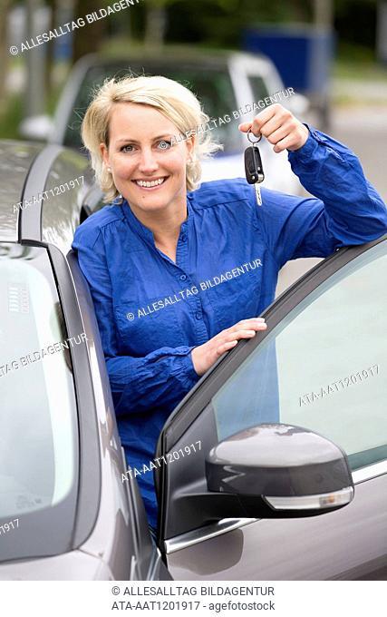 Female car driver is holding a car key