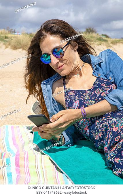 brunette woman with sunglasses and blue clothes smiling and touching mobile phone smartphone ,or texting, lying on towel on the beach