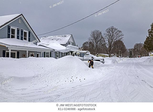 Grand Marais, Michigan - A woman shovels snow in front of a residence. The town, on the shore of Lake Superior, gets an average of 151 inches of snow per year