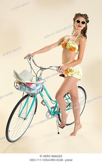 Beach pin-up girl standing next to bicycle