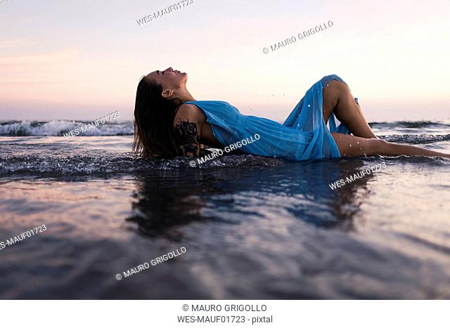 Young tattooed woman wearing blue dress lying in water at seashore by sunset