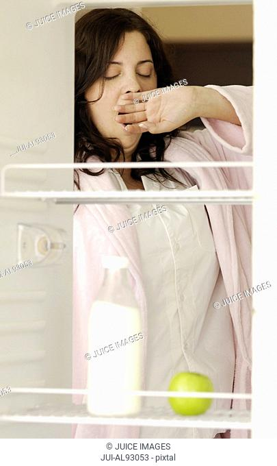 Yawning woman looking in refrigerator