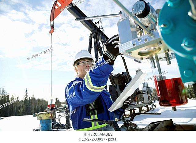 Female engineer with clipboard checking drilling rig equipment