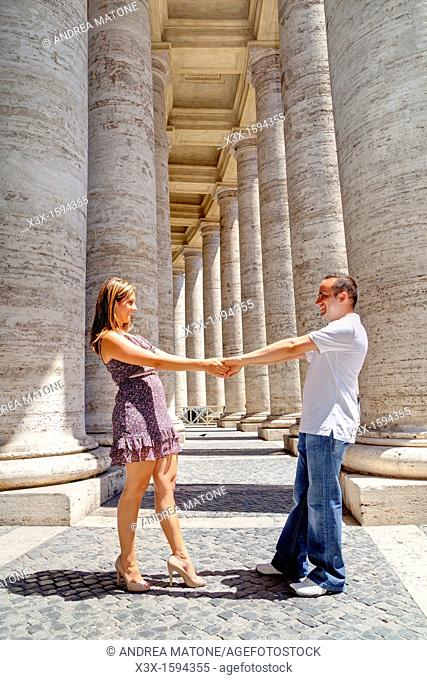 Couple dancing underneath the columns of Saint Peter's square Vatican Rome Italy