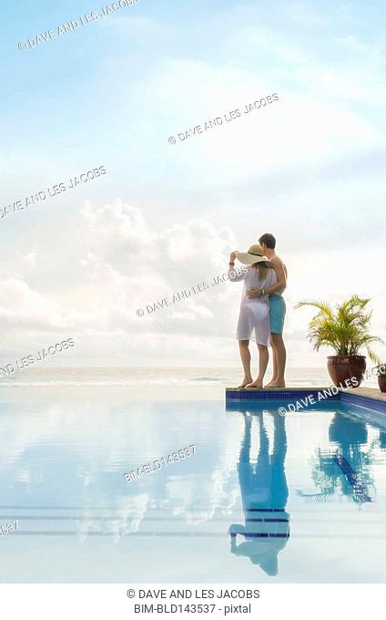 Caucasian couple admiring view from swimming pool