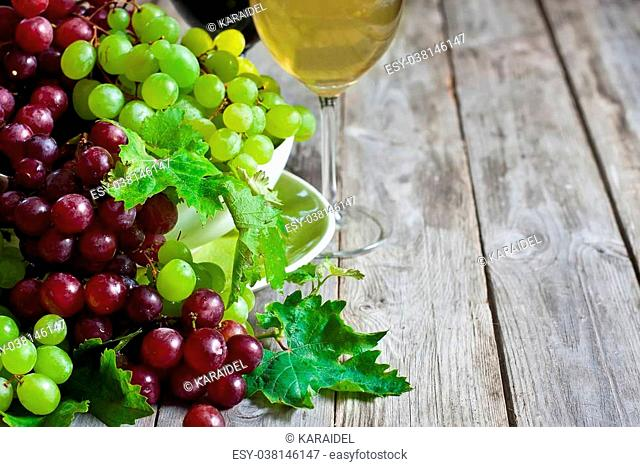 Ripe green and red grape and white and red wine in goblets. Copy space background