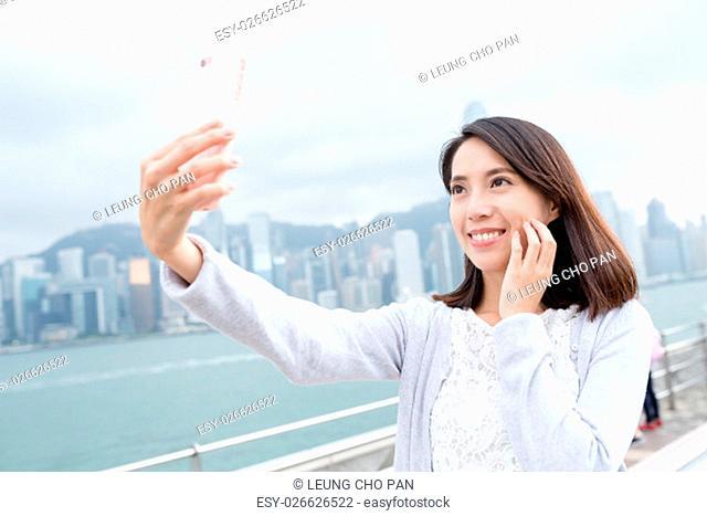 Woman taking selfie in Hong Kong city