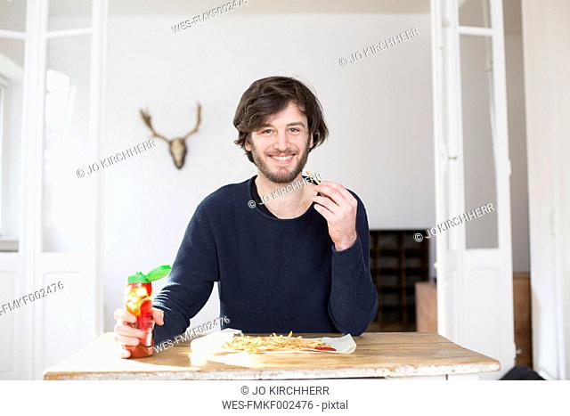 Portrait of smiling young man eating French fries with ketchup