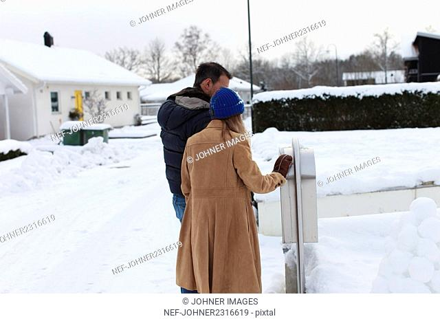 Young couple checking mailbox in winter