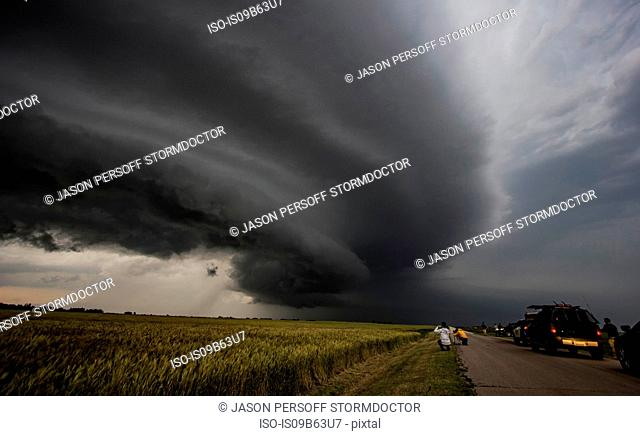Storm chasers watching arcus cloud and shelf cloud over rural area, Enid, Oklahoma, United States, North America