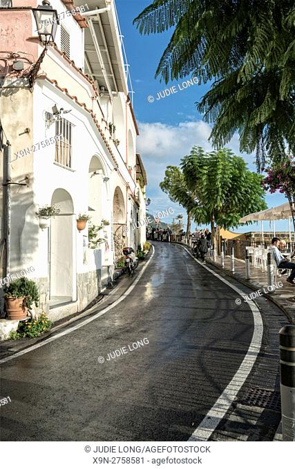 Looking at a Street in Positano, Amalfi Coast, Italy, lined with shops, cafes and people dining across the street at cafe tables