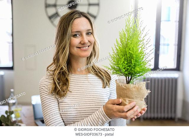 Portrait of smiling woman holding plant at home
