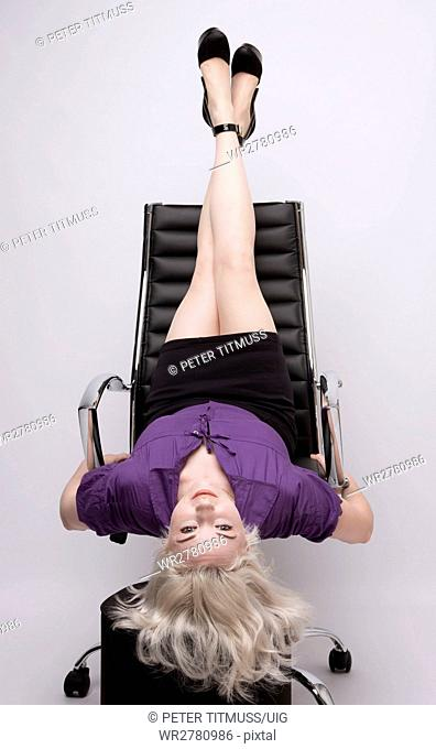 Secretary taking time out with her legs stretching exercise on the back of an office chair