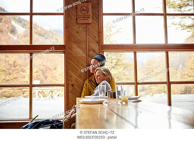 Chile, Torres del Paine National park, mother with son sitting at table in a mountain hut