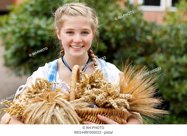 Germany, Luneburger Heide, portrait of smiling blond girl with basket of cereals