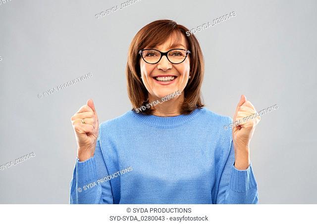 portrait of happy senior woman celebrating triumph