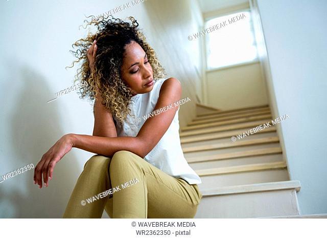Tensed woman sitting on stairs