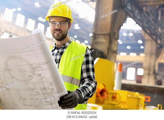 Portrait smiling engineer with blueprints ins steel factory