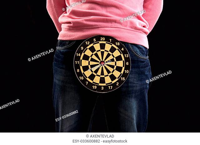 Teenager holding a dartboard with his hands