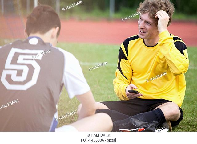 Young sportsman sitting with friend on soccer field