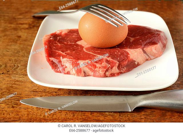 Whole brown egg in shell and ribeye steak on white plate with knife and fork. Eggs and meats are integral parts of the Paleo Diet