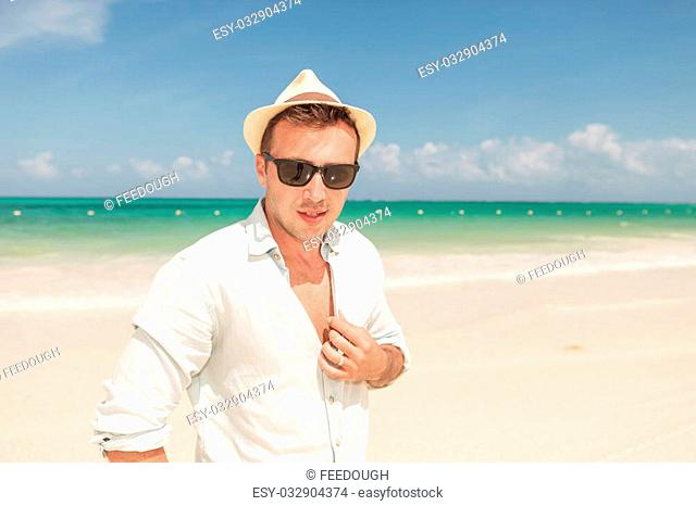 Attractive young man posing on the beach while fixing his shirt