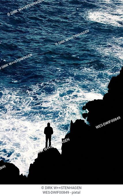 Portugal, Madeira, silhouette of man at rocky coast by the sea