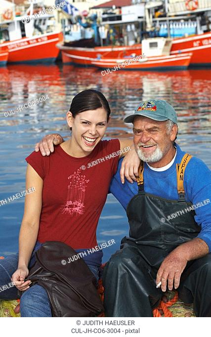 Young girl and fisherman sitting together on fishing nets laughing fishing boats in background