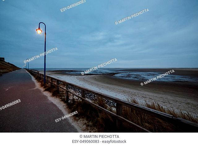 Long dark grey asphalt road between grassy hill and scenic beach next to baltic sea shoreline in summer evening with glowing lanterns