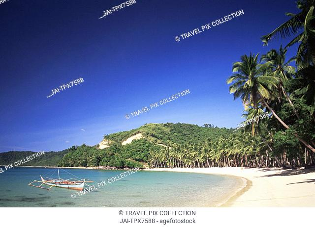 Philippines, Palawan, Bascuit Bay, El Nido, Outrigger on Tropical Beach at Sunset