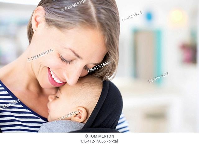 Mother holding sleeping baby boy