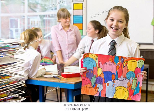 Portrait confident middle school student showing painting in art class