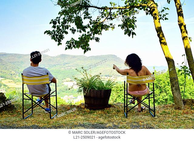 Rear view of a couple sitting on folding chairs and looking away. Catalonia, Spain