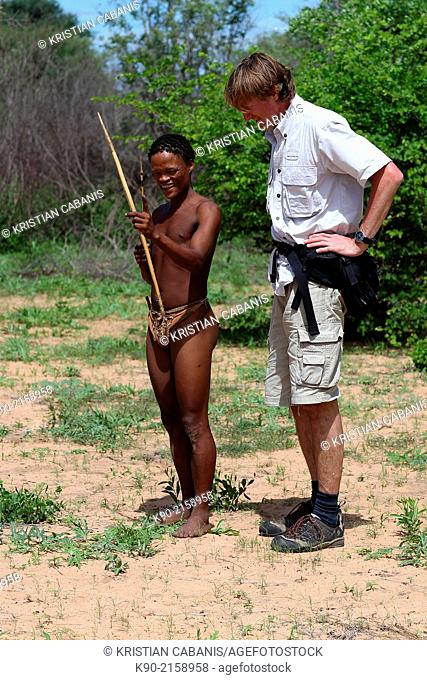 Ju/'hoansi San man explaining to tourist how to use bow and arrow, Namibia, Africa
