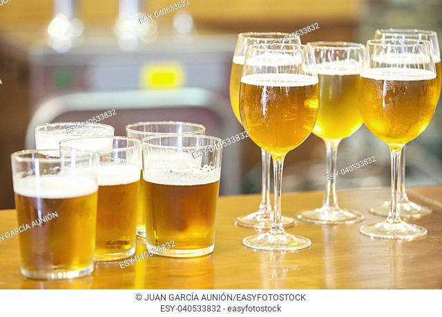 Glasses and glass chalices of beer over bar counter. Selective focus