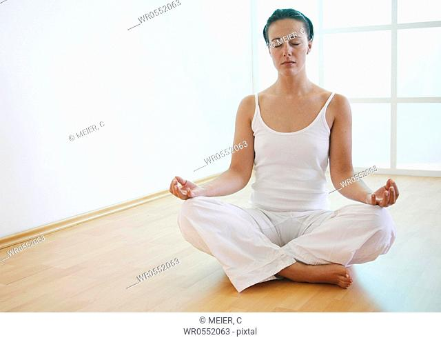 Young woman meditates on the floor