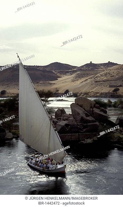 Felucca with tourists on the river Nile, in front of the Sahara Desert, near Aswan, Egypt, North Africa, Africa